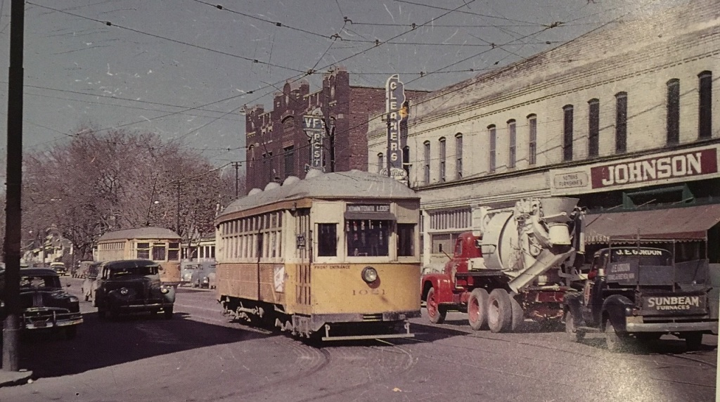 This is a picture of the building at North 24th and Ames. Richard Orr took it in the 1950s to highlight the streetcar. Behind that, you can see the Druid Hall, which is now on the National Register of Historic Places; a cleaners; the Star Liquor Store; and LaRue's Barbershop. Johnson's was a Rexall Drug Store.