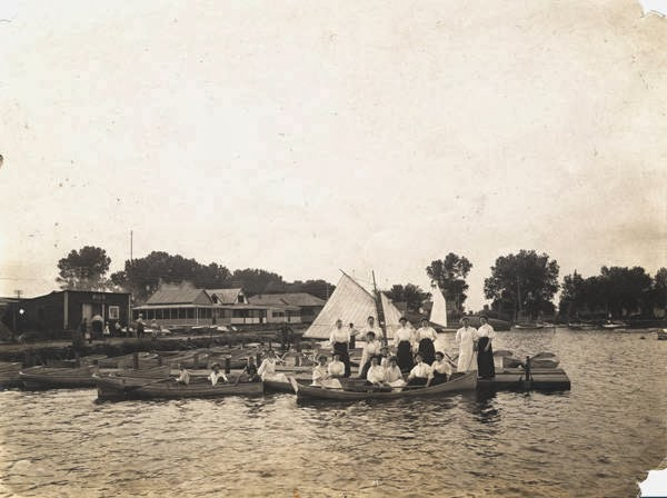A historic photo of boaters on Lake Nakoma and bungalows in the background.