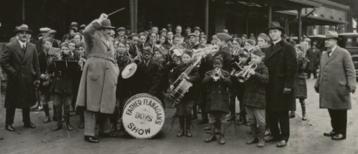 This is Father Flanagan's Boy's Town Band with Dan Desdunes on the far left, Paul Whiteman in the middle, and Father Flanagan in the black coat on the right.