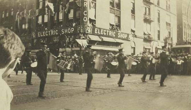 This is a 1920 image of the Dan Desdunes Band playing during a parade in downtown Omaha.