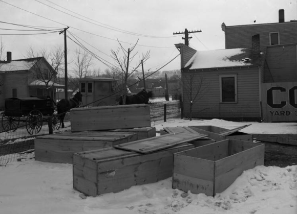 Several coffins are waiting next door to the Obee Funeral Home on Lake Street, including one for a child. The dark wagon to the left is a hearse for the O'Bee Mortuary, owned and operated by an African American for African Americans in Omaha's highly segregated atmosphere.