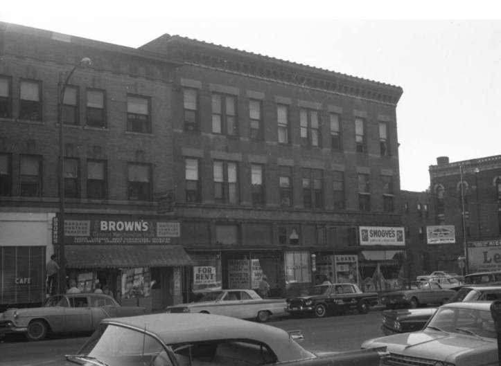 This 1960s era pic is two blocks north of Dodge Street at Davenport Street. The big building was the Wright Block Apartments at 318 North 16th Street. Also visible is Brown's Merchandise Bazaar, an empty pawn shop, Paul's Barbershop, Smogye's Groceries, and Webster's Bar on the corner. There's Richman Gordman billboard to the right, across the street from the bar.