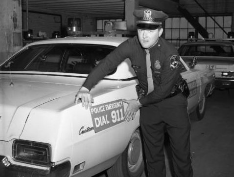 An officer with the Omaha Police Department leans against his car in 1970.
