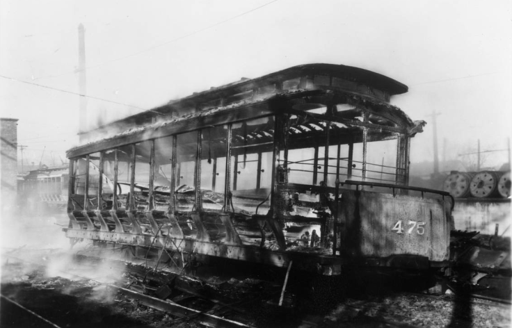 Omaha Streetcar Company car 475 lies smoldering after being demolished by rioting strikers in 1935.