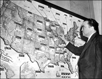 J Edgar Hoover facing a map