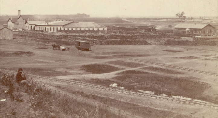"This stereograph may be the earliest image of North 11th and Burt looking over the Union Pacific Railroad shops. Apparently this picture was taken in Omaha in 1866. A man sits on a grassy hill near railroad tracks and Union Pacific Railroad works buildings and depot behind him. An engine is in front of the depot and a freight car is near a horse drawn wagon. There are frame and brick warehouse buildings and a roundhouse, piles of wood around the rail yard, and standing water beside tracks. Others have speculated that the large lone tree just above the building to the right could possibly be the tree that Omaha's ""Lone Tree Ferry"" was named after. Some believe the ferry to be near the Gallup Building, which would have placed it just about where that tree is. I think the short white area just left of the tree is is the Missouri River and the dark line above it is where Eppley Field is now."