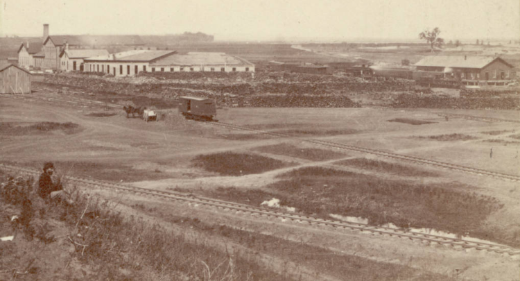 """This stereograph may be the earliest image of North 11th and Burt looking over the Union Pacific Railroad shops. Apparently this picture was taken in Omaha in 1866. A man sits on a grassy hill near railroad tracks and Union Pacific Railroad works buildings and depot behind him. An engine is in front of the depot and a freight car is near a horse drawn wagon. There are frame and brick warehouse buildings and a roundhouse, piles of wood around the rail yard, and standing water beside tracks. Others have speculated that the large lone tree just above the building to the right could possibly be the tree that Omaha's """"Lone Tree Ferry"""" was named after. Some believe the ferry to be near the Gallup Building, which would have placed it just about where that tree is. I think the short white area just left of the tree is is the Missouri River and the dark line above it is where Eppley Field is now."""